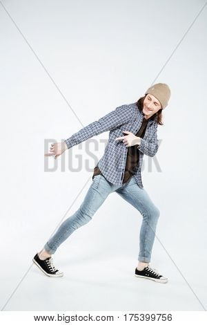 Vertical image of hipster which pointing and looking down. Isolated gray background