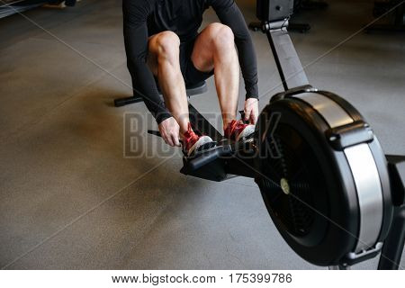 Cropped image of athletic man which using rowing machine in gym
