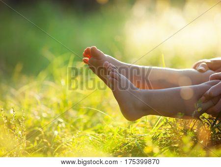 Children's feet on  green grass outdoors in spring park