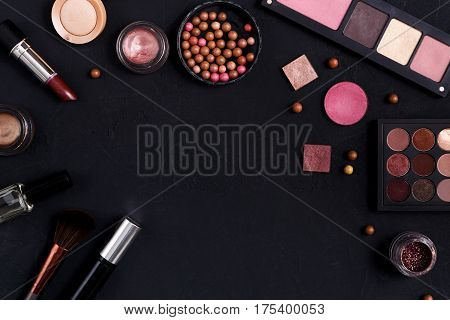 Makeup cosmetics, brush and other essentials frame on black background. Top view, flat lay with copy space. Beauty tools palettes collection, lipstick, eyeshadow, ball blush, foundation and more