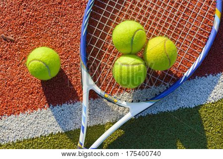 Tennis Racket and Balls on a Tennis Court