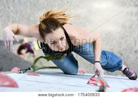 Beautiful female Climber moving up on vertical climbing Wall at qualification round of National Climbing Competitions