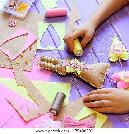 Small girl shows a felt bunny in hands. Girl made a felt cute bunny with hearts for Easter. Tools and materials for kids creativity on a wooden table. Simple Easter crafts idea for kids