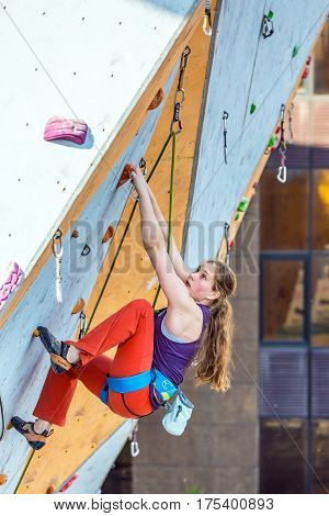 Junior female Athlete makes hard move on climbing Wall of National Competition with very emotional face. Dnipro, Ukraine, May 20, 2016