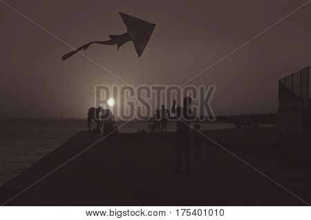 Silhouettes of father and son flying a kite in sunset by the sea with fishermen behind