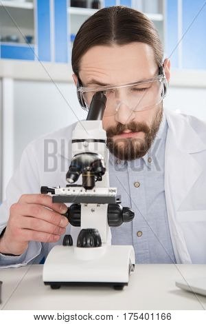 Young man in protective glasses looking in microscope in laboratory