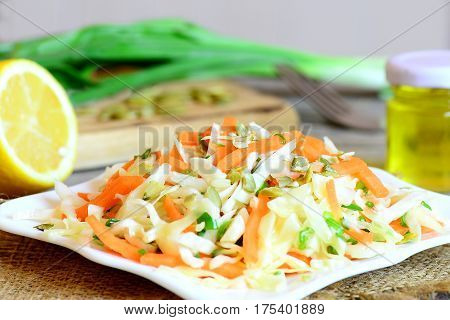 Simple coleslaw salad. Coleslaw salad with fresh carrots, green onion and pumpkin seeds on a plate. Salad ingredients on a wooden table. Healthy vegetable food. Closeup