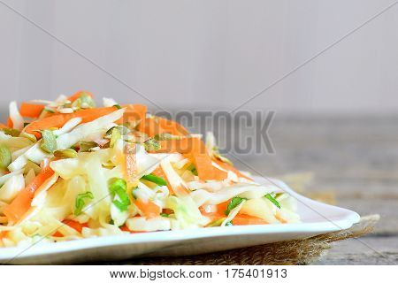 Healthy homemade coleslaw salad. Delicious coleslaw salad with carrots, green onion and pumpkin seeds on a plate and on a wooden table. Fresh vegetable dish. Closeup