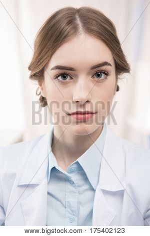 Young professional female scientist in lab coat looking at camera