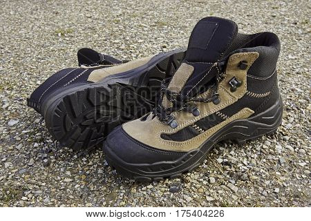 Pair of hiking boots for women on a surface of broken shells from a walking-trail.
