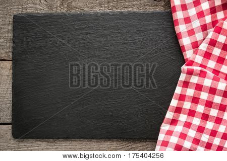Rustic wooden boards red checkered napkin and black slate dish with copy space for your menu or recipe. Menu card for restaurants.