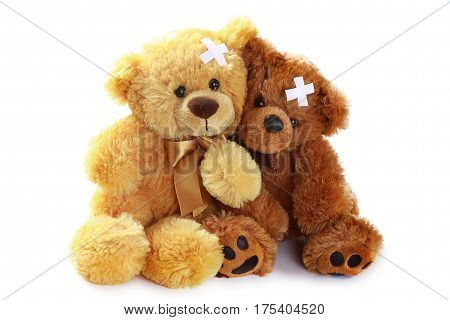 Two Teddy Bears with Crossed Adhesive Bandages on Head