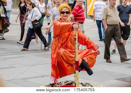 VIENNA AUSTRIA - JUNE 6 2012: beautiful girl demonstrates trick of levitation at Vienna's street. Austria