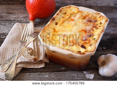 Vegetable pumpkin gratin with cheese in ceramic bakeware rustic style