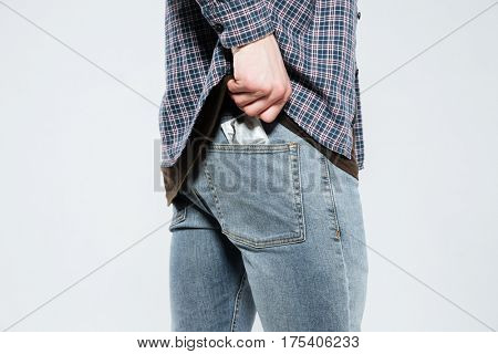 Cropped image of hipster which laying condom in back pocket. Isolated gray background