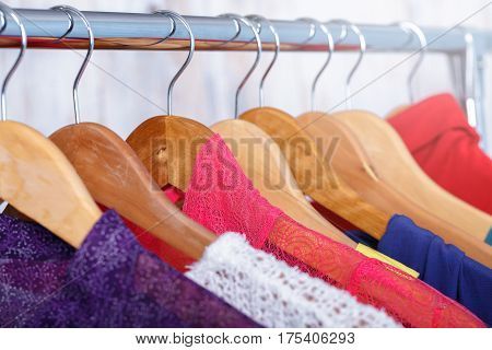 colorful womens clothes on wood hangers on rack in a fashion store. women's closet