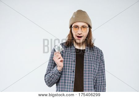 Young hipster in eyeglasses which holding condom in hand and looking at camera. Isolated gray background