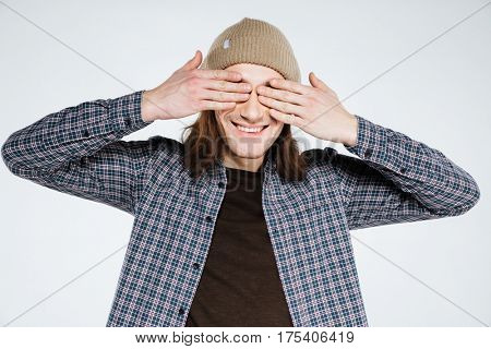 Smiling hipster which covering his eyes with both hands. Isolatated gray background