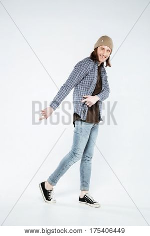 Vertical image of Hipster which pointing away and down while looking at camera. Full length portrait