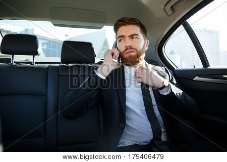 Handsome young business man talking on mobile phone and touching his necktie while sitting in back seat of a car