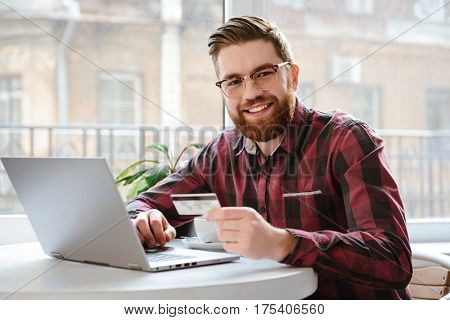 Image of amazing bearded young man sitting in cafe while using laptop computer and holding debit card. Looking at camera.