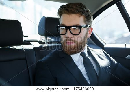 Portrait of a srious young man wearing suit and eyeglasses whie sitting in car