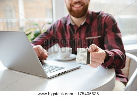 Cropped photo of cheerful bearded young man sitting in cafe while using laptop computer and showing debit card to camera.