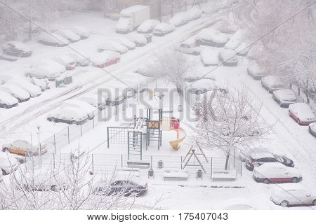 Chidren playground and cars covered with snow