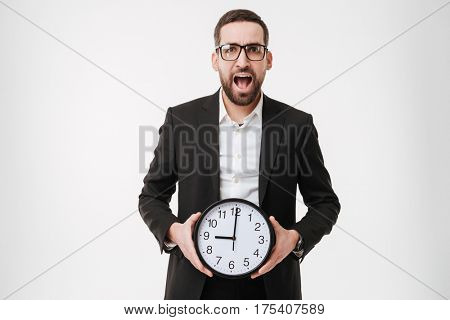 Photo of young screaming bearded businessman over white background holding watch. Looking at camera.