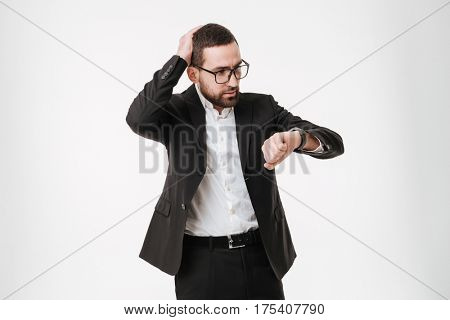 Image of confused young bearded businessman posing over white background while looking at watch.