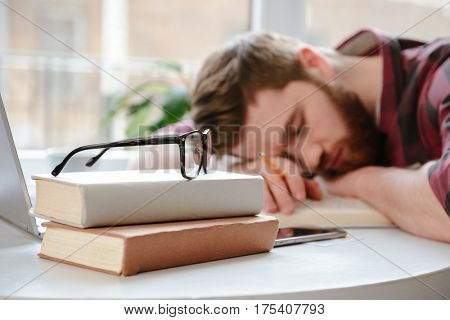 Photo of sleeping bearded young man student lies on hands in cafe near books and glasses. Focus on books with glasses.