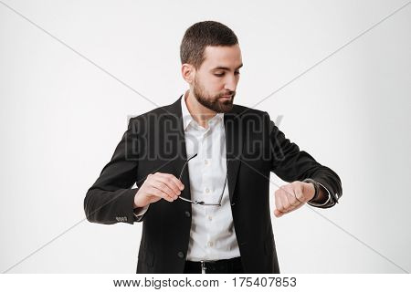 Image of serious young bearded businessman posing over white background while looking at watch.