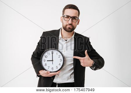 Photo of young handsome bearded businessman over white background pointing to watch. Looking at camera.