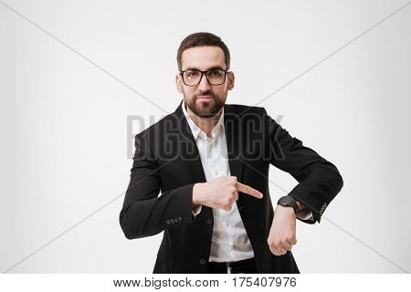 Image of serious young bearded businessman posing over white background while showing his watch. Looking at camera.