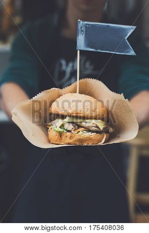 Fresh burger cooked at barbecue outdoors. Cookout american bbq with text flag. Big hamburger with steak meat and vegetables closeup with chef unfocused at background. Street fast food.