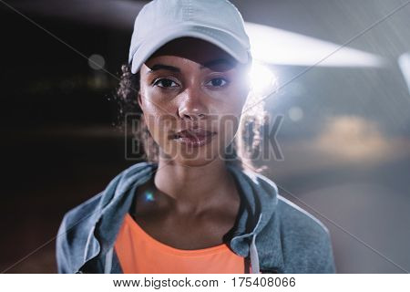 Urban female runner in city at night. Female in sportswear and cap standing outdoors and looking at camera.