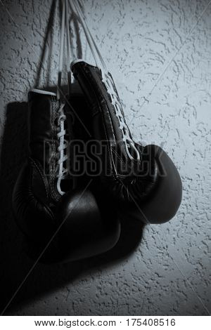 A Pair of Black Boxing Gloves Hang on Nail on a Wall