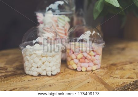Desserts choice. Marshmallow chewing candies in glass jars on counter bar. Traditional american sweets for sale, closeup