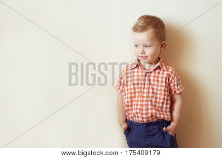 Little boy stands in a shirt and slacks, hands in pockets