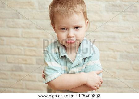 Little boy standing with folded hands against a brick wall. The concept of resentment, frustration, disappointment, sadness