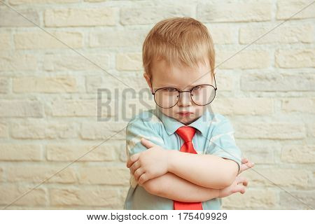 Little boy standing with folded hands against a brick wall. The concept of resentment, frustration, disappointment, sadness, problem