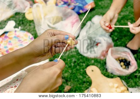 Woman Making Appetizers Putting Cheese Olives Tomatos On Wooden Stick, Picnic Kitchen Outdoors, Cate