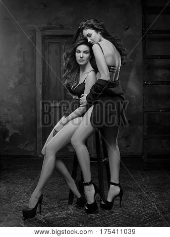Two beautiful women in black erotic lingerie on white studio background. black and white photo