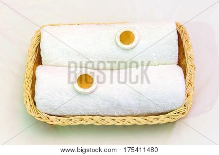 Two white towels and small soaps in wicker basket good accommodation of hotel service.