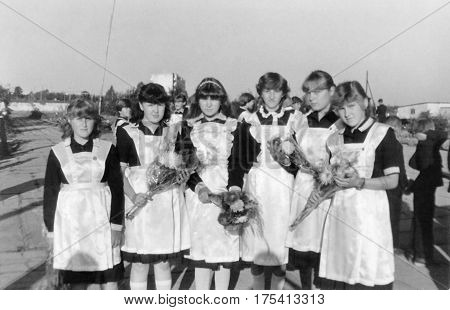 SENNO BELARUS - SEPTEMBER 1 1985: Schoolgirls-tenth graders in elegant school uniform with bouquets of flowers on September 1st (1985) Senno Belarus