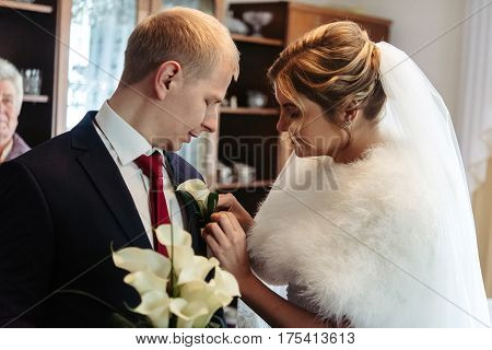 Gorgeous Luxury Blonde Bride Putting On Boutonniere On The Suit Of Stylish Groom