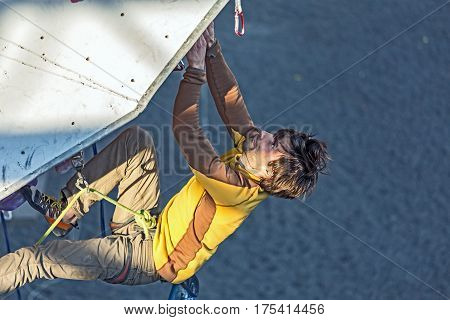Male hippie style Climber hanging on climbing Wall of national Competitions. Dnipro, Ukraine, May 20, 2016