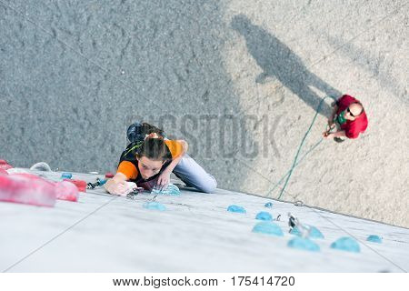 Junior female Athlete climbs Competition route and belaying referee watching her from below. Dnipro, Ukraine, May 21, 2016
