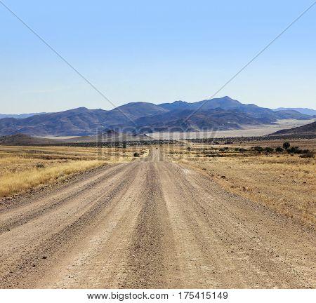 Adventurous drive on a rough gravel road through the desert towards the mountains.