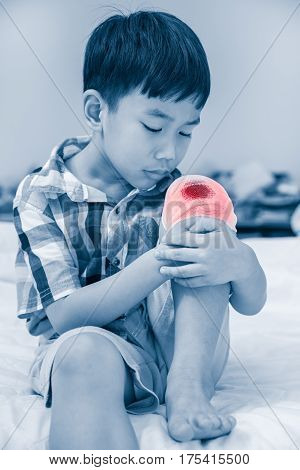 Child injured. Asian boy looking at wound on his knee with bandage bandage in focus. Children have been an accident. Human healthcare concept. Color increase blue skin and red spot indicating of pain
